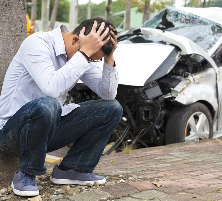 Immediately after a car crash, a man with confusion is sitting in the pathway with hands-on his heads