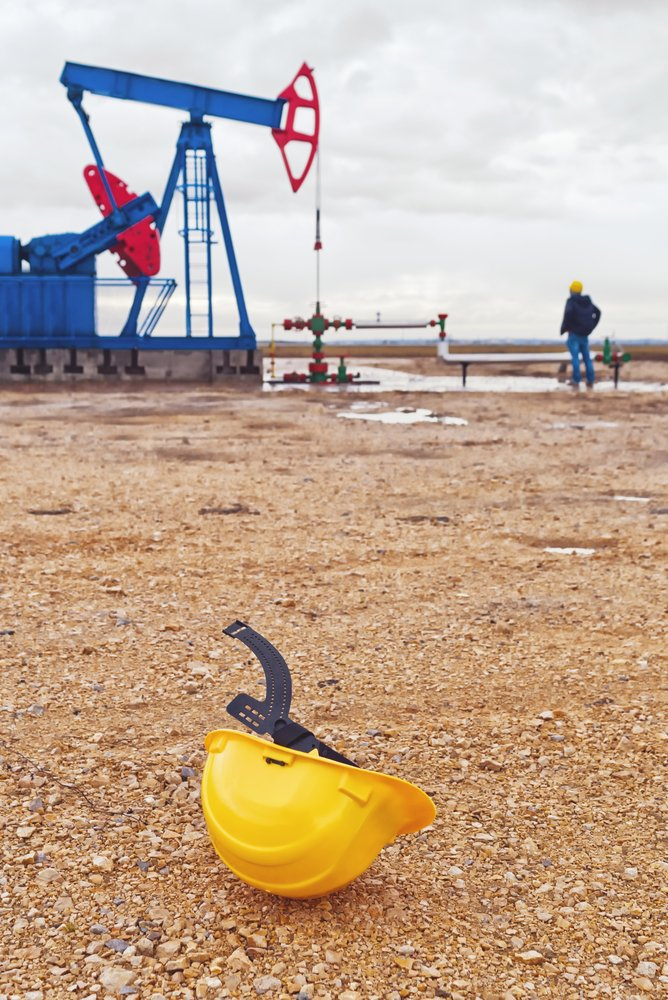 oilfield accident lawyers wearing yellow colour helmet inspecting the accident spot